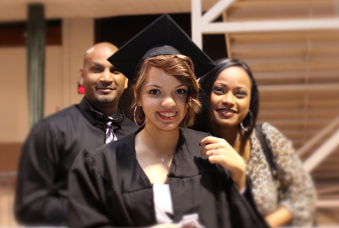 A young woman at her high school graduation with her family.