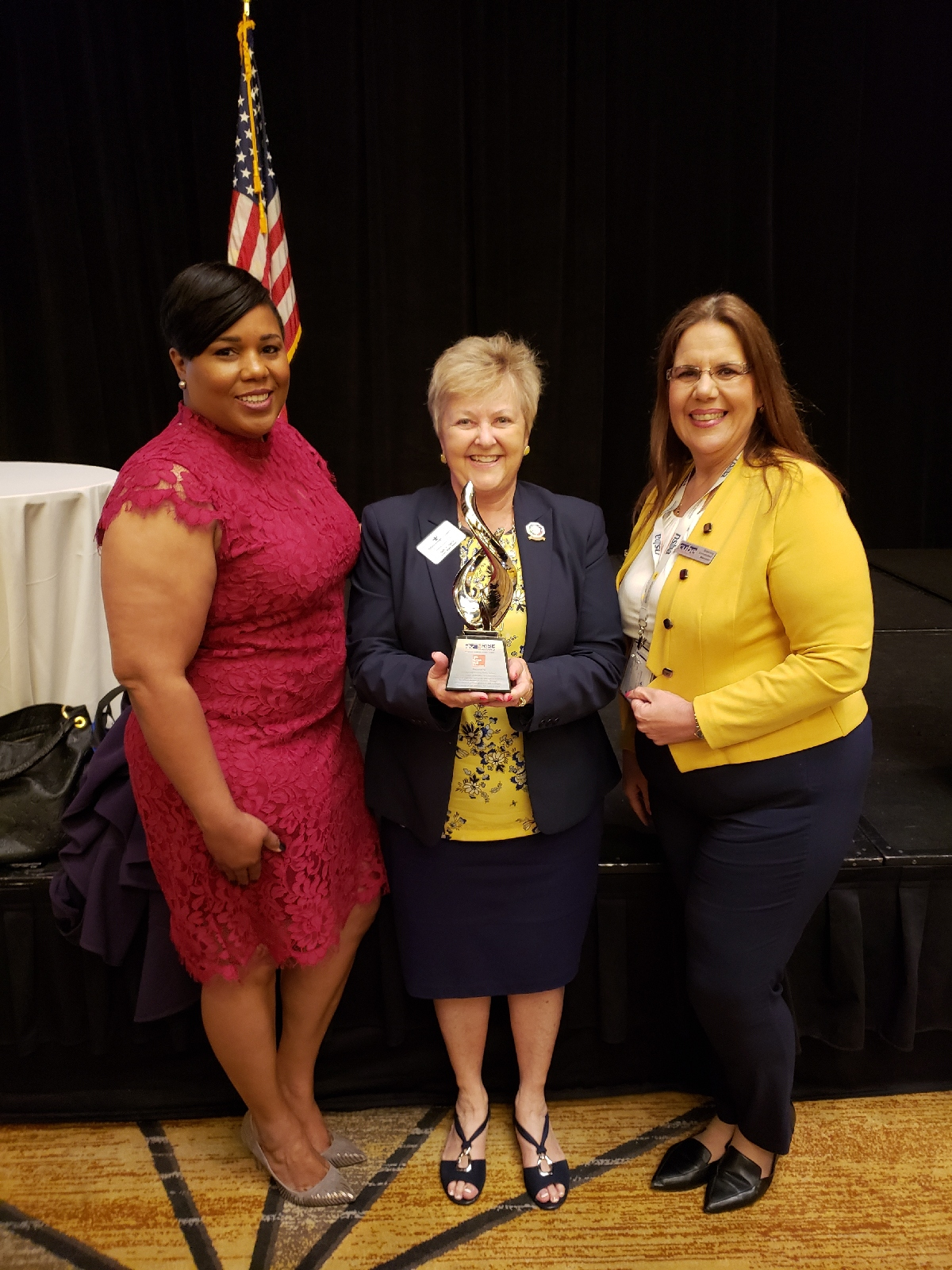 School Board Vice Chair Tamara Shamburger, School Board Chair Sally Harris and School Board Member Susan Valdes accept the RISE award.